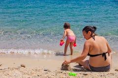 Mãe e filha que sentam-se na praia, jogando com a areia em férias de verão imagens de stock royalty free