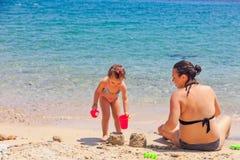 Mãe e filha que sentam-se na praia, jogando com a areia em férias de verão fotografia de stock
