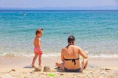 Mãe e filha que sentam-se na praia, jogando com a areia em férias de verão foto de stock royalty free
