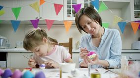 Mãe e filha que sentam-se na tabela e que crafting o ninho com ovos coloridos junto e que luaghing na cozinha com video estoque