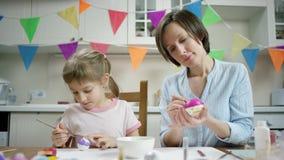 M?e e filha que sentam-se na tabela e que crafting o ninho com ovos coloridos junto e que trabalham na cozinha video estoque