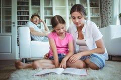 Mãe e filha que sentam-se no assoalho e que olham o álbum de fotografias imagem de stock