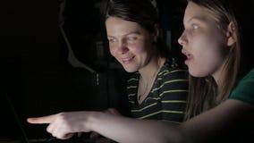 Mãe e filha que sentam-se no portátil e que têm o divertimento junto 4k UHD vídeos de arquivo