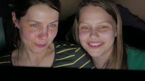 Mãe e filha que sentam-se no portátil e que têm o divertimento junto 4k UHD video estoque