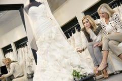 Mãe e filha que sentam-se no sofá ao olhar o vestido de casamento elegante na loja nupcial Fotografia de Stock Royalty Free