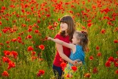 A mãe e a filha que sorriem em uma papoila colocam O piquenique no campo da papoila Caminhada com a família no campo da papoila A foto de stock