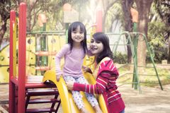 Mãe e filha que sorriem nas corrediças exteriores foto de stock
