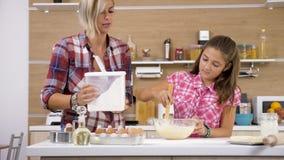 Mãe e filha que têm o divertimento e que cozinham junto vídeos de arquivo