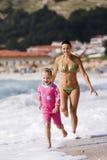 Mãe e filha que têm o divertimento no oceano Imagens de Stock Royalty Free
