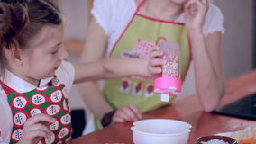 Mãe e filha que têm o divertimento que faz junto cookies na cozinha filme