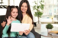 Mãe e filha que usa o bate-papo video na tabuleta imagens de stock
