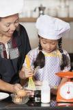 Mãe e filha que usa o batedor de ovos para misturar a farinha do ovo e de trigo imagens de stock royalty free