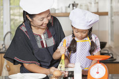 Mãe e filha que usa o batedor de ovos para misturar a farinha do ovo e de trigo foto de stock