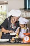 Mãe e filha que usa o batedor de ovos para misturar a farinha do ovo e de trigo fotos de stock royalty free