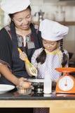 Mãe e filha que usa o batedor de ovos para misturar a farinha do ovo e de trigo imagens de stock