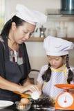 Mãe e filha que usa o batedor de ovos para misturar a farinha do ovo e de trigo imagem de stock