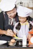 Mãe e filha que usa o batedor de ovos para misturar a farinha do ovo e de trigo imagem de stock royalty free