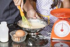 Mãe e filha que usa o batedor de ovos para misturar a farinha do ovo e de trigo fotos de stock