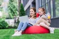 mãe e filha que usa o portátil ao descansar no saco imagens de stock