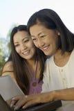 Mãe e filha que usa o portátil fora imagem de stock royalty free