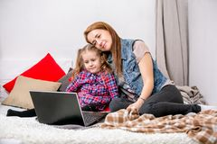 Mãe e filha que usa o portátil na cama no quarto A mãe abraça sua filha com amor e cuidado, e sorriem ao olhar t imagens de stock royalty free