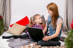 Mãe e filha que usa o portátil na cama no quarto Olham se e sorriem foto de stock royalty free