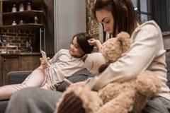 mãe e filha que usa smartphones ao descansar no sofá foto de stock