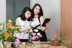 Mãe e filha que usa a tabuleta digital ao arranjar floresce imagens de stock