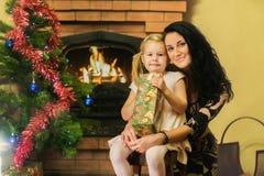 A mãe e a filha receberam presentes do ano novo Idade 5 anos imagem de stock royalty free