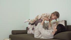A mãe e a filha relaxam no sofá em casa filme