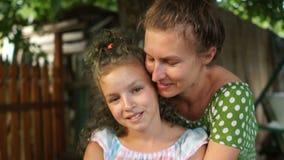 Mãe e filha, retrato próximo em um pátio da vila Uma menina e uma mulher são vestidas nos sundresses do verão, abraçando filme