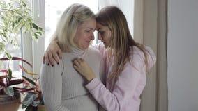 A mãe e a filha são abraçando e tristes filme