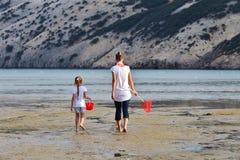 A mãe e a filha sejam redes de pesca no mar Fotografia de Stock Royalty Free