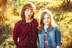 A mãe e a filha sentam-se pelo rio Imagem de Stock Royalty Free
