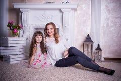 A mãe e a filha sentam-se perto da chaminé Foto de Stock Royalty Free