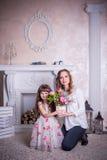 A mãe e a filha sentam-se perto da chaminé Fotografia de Stock Royalty Free