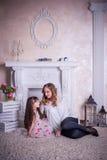 A mãe e a filha sentam-se perto da chaminé Fotos de Stock Royalty Free