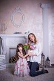 A mãe e a filha sentam-se perto da chaminé Fotos de Stock