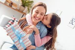 A mãe e a filha serem de mãe em casa à filha de assento do dia do ` s que abraça a mamã que guarda o beijo atual imagens de stock royalty free