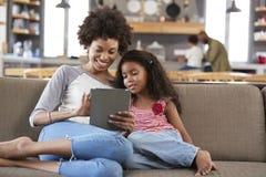 Mãe e filha Sit On Sofa In Lounge que usa a tabuleta de Digitas fotografia de stock