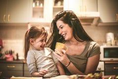 A mãe e a filha têm o divertimento na cozinha home imagens de stock