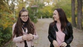 Mãe e filha um adolescente que dá uma volta através das aleias no parque do outono vídeos de arquivo