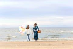 Mãe e filha unidas que mantêm as mãos e que contemplam o mar foto de stock
