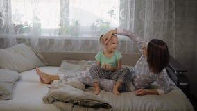 A mãe e a filha vestiram-se nos pyjamas apreciam-se na cama em casa na manhã A mamã feliz é cabelo tocante dela video estoque