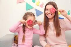 A mãe e a filha weekend junto em casa cobrindo os olhos com os pirulitos fotografia de stock