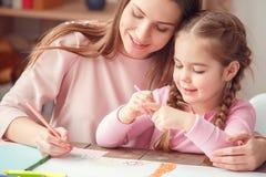 A mãe e a filha weekend junto em casa o conceito da educação que senta-se na tabela que abraça o desenho fotografia de stock