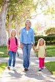 Mãe e filhas que andam à escola na rua suburbana imagens de stock