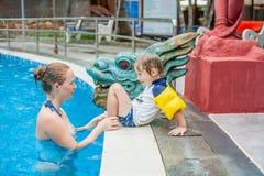 Mãe e filho alegres novos em uma piscina imagens de stock