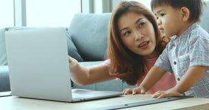 Mãe e filho asiáticos que usa o caderno video estoque