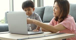 Mãe e filho asiáticos que usa o caderno, a seguir olhando o vídeo filme